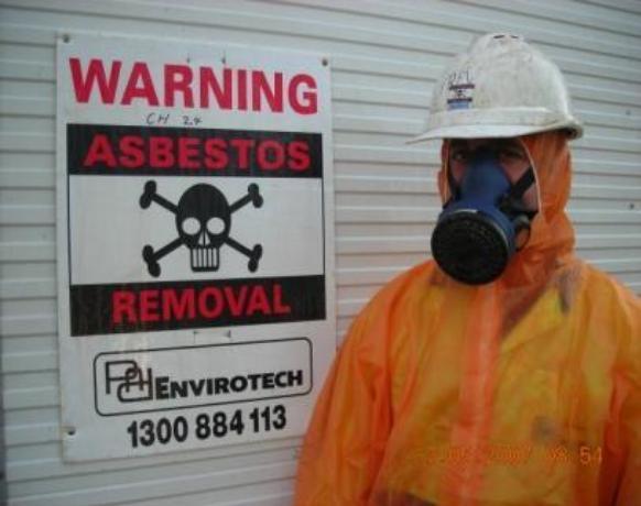 Man-in-HazMat-Suit-in-front-of-Asbestos-Warning