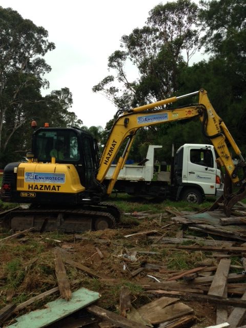 Excavator participating in site clean up